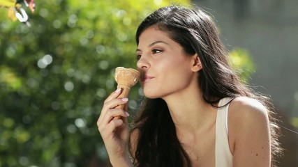 Young woman enjoying an Italian ice cream outdoors.