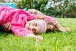 Happy little girl lying on grass