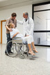 Doctor laughing with pregnant woman in wheelchair and partner