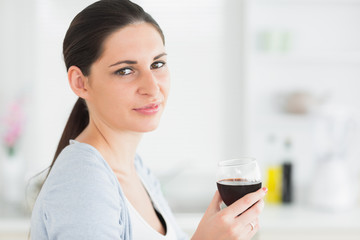 Smiling woman holding glass of red wine