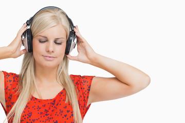 Blonde in orange dress listening to music