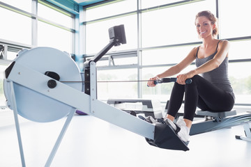 Woman training happily on row machine