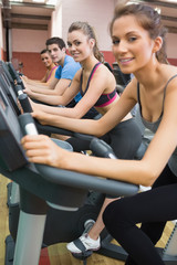 Three woman and one man on exercise bikes