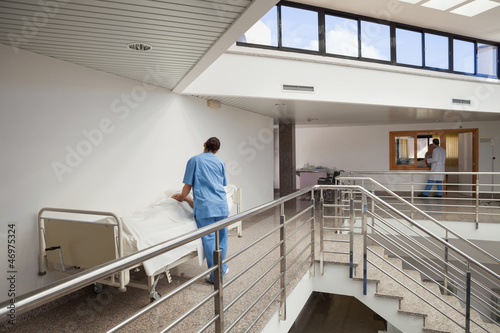 Nurse tending to patient in bed in corridor