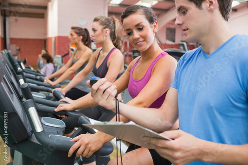 Instructor showing stopwatch in gym