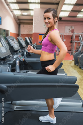 Smiling woman running on a treadmill in the gym