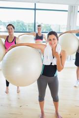 Women holding exercise balls