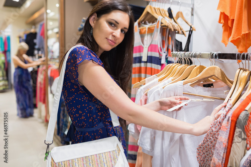 Woman with bag looking through clothes and smiling