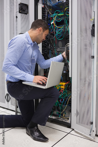 Man fixing wires while doing maintenance in data center