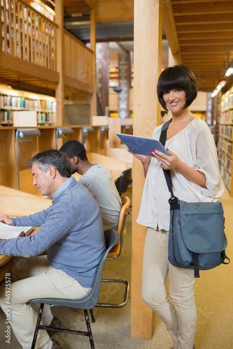 Woman with tablet pc in library