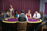 People sitting at the poker table playing