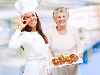 Two Happy Female Chef Presenting Muffins