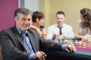 Man with cigar taking break from roulette table