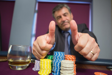 Man giving thumbs up sitting at roulette table