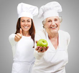 Senior Chef Holding Apple In Front Smiling Chef