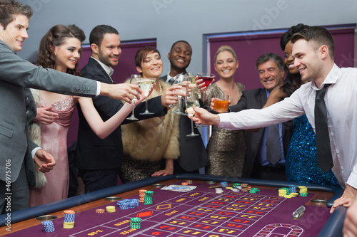 People standing clinking glasses at roulette table