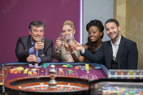 Four people toasting with champagne at roulette