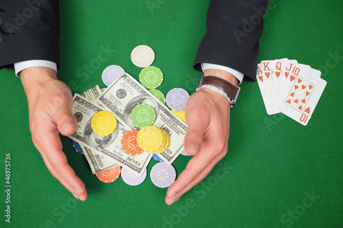 Hands grabbing dollars and chips from table beside royal flush