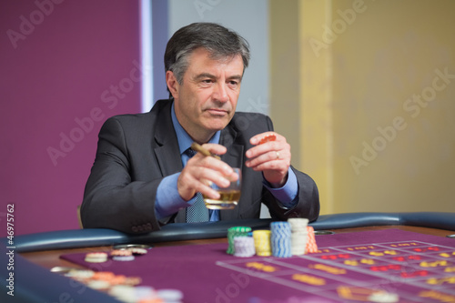 Man looking at the roulette table looking angry