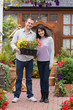 Smiling couple holding tray of plants