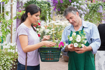 Woman carrying a basket while buying flowers and talking to empl