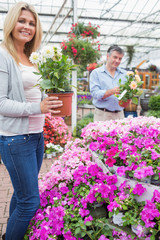 Couple holding plants while smiling