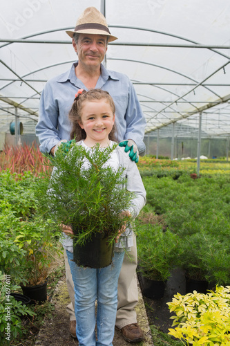 Little girl holding potted plant with grandfather