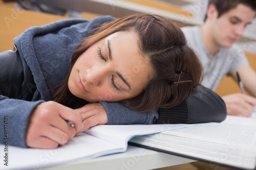 Woman leaning at the desk at the lecture hall