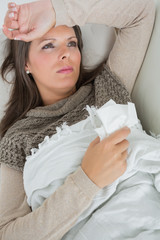 Ill woman lying on sofa