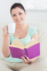 Woman sitting on the couch and reading while drinking