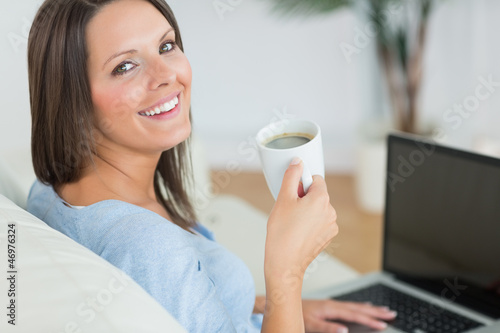 Brunette using her laptop and drinking a cup of coffee