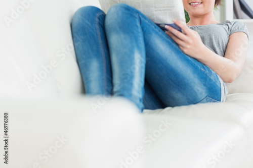 Woman lying on the couch and reading newspaper