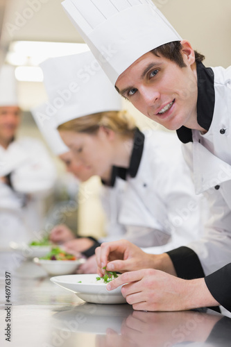 Chef looking up from preparing salad