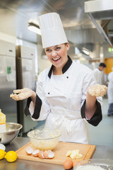 Laughing baker showing hands covered in dough