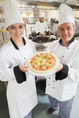 Chef's presenting a pizza