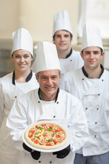 Chef presenting pizza with others behind him