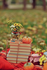 outdoors ripe pumpkin and a stack of books with a bouquet of aut