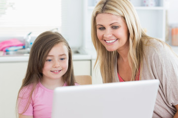 Woman and girl looking at the laptop monitor