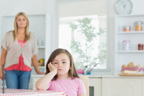 Child at kitchen table looking angry