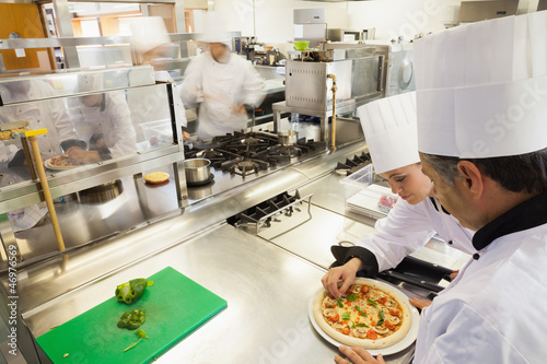 Cooks preparing pizza