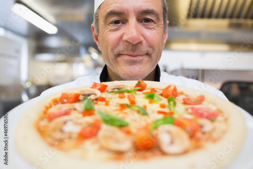 Chef showing a pizza