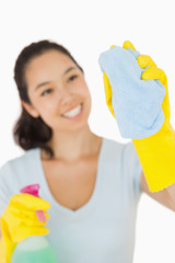 Happy woman cleaning a window
