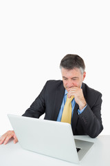 Thoughtful man sitting at his desk with laptop