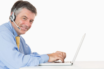 Smiling man with headphones typing on his laptop