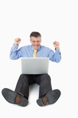 Cheering man with laptop on the floor