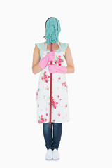 Woman in apron hiding her face with a mop
