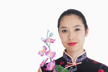 Woman holding an orchid while smiling