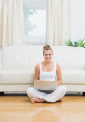 Joyful woman sitting on the floor with laptop