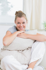 Woman holding pillow and smiling