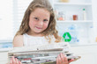 Girl holding old newspapers in the kitchen